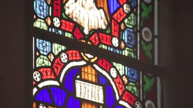Tilt down of Jesus in a stain glass window