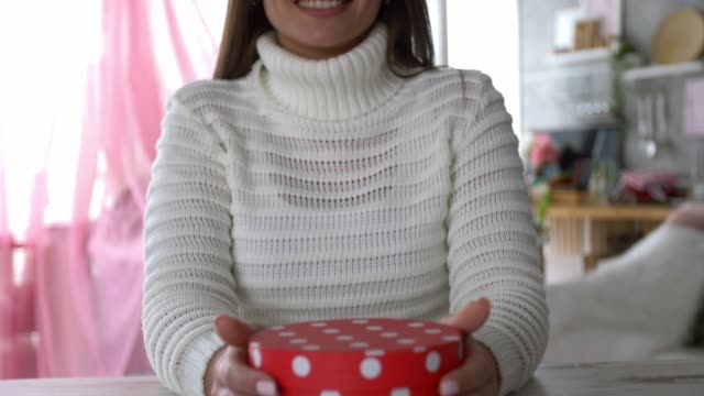 tilt down of smiling young woman holding a polka dot gift box - polka dot stock videos & royalty-free footage