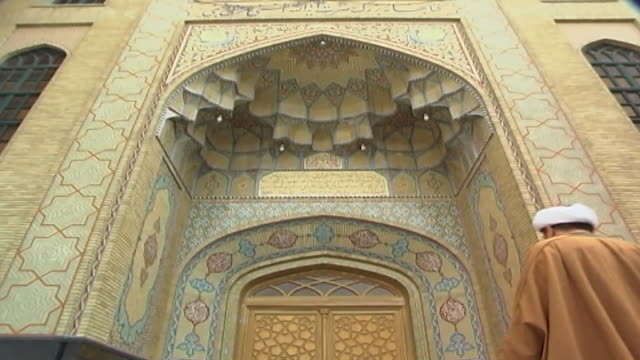tilt down on a shiite cleric walking up to the arched entrance - a vaulted iwan - of the marachi najafi library in qom. the library is the third... - number 8 stock videos & royalty-free footage