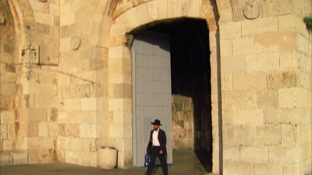 vídeos de stock, filmes e b-roll de tilt down on man walking - jerusalém