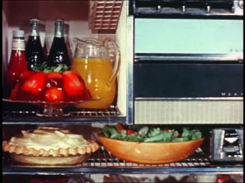 1958 tilt down open refrigerator filled with food