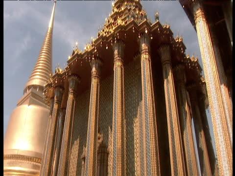 tilt down oriental temple to small buddha statue at base bangkok - bangkok stock videos & royalty-free footage