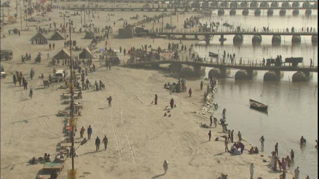 Tilt down over banks of Ganges crowded with Kumbh Mela pilgrims, Allahabad, Uttar Pradesh, India