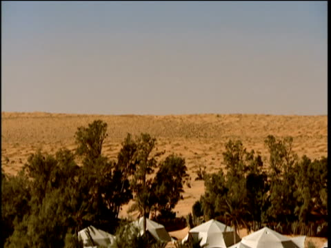 tilt down over holiday camp in sahara desert tunisia - holiday camp stock videos & royalty-free footage