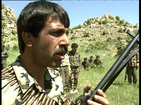 tilt down over pkk soldier holding rifle and bullets bekaa valley lebanon; 1991 - クルド人点の映像素材/bロール