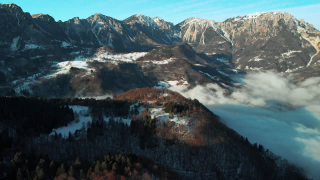 tilt down over the foggy valley with high peaks mountain in the background during winter - autumn stock videos & royalty-free footage
