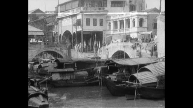 vidéos et rushes de tilt down pan right chinese men pole boats though a canal in an urban scene / pan right of chinese people crossing a bridge and canal / pan left... - jonque