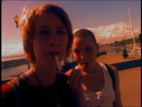 tilt down pan to close up two girls laughing / one smoking cigarette, one with shaved head / lausanne, switzerland - zigarette stock-videos und b-roll-filmmaterial