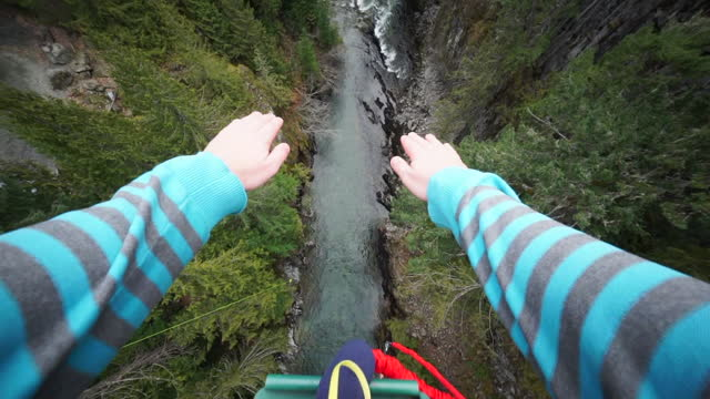 tilt down panning shot of tourist bungee jumping over river in forest during vacation - british columbia, canada - named wilderness area stock videos & royalty-free footage