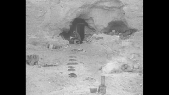 vídeos de stock e filmes b-roll de tilt down people searched other bombed buildings for dead / ls man sits in cave opening / cu man and four children emerge from cave / cu distraught... - guerra civil