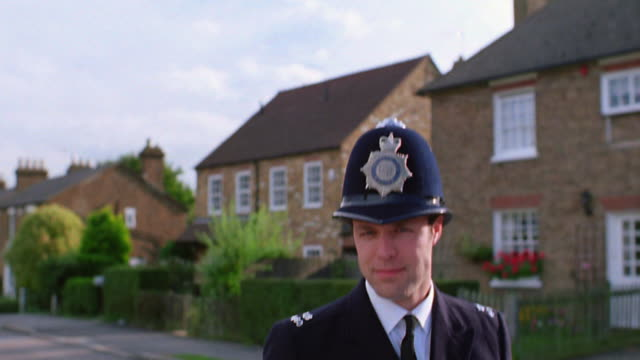 tilt down portrait bobby standing on neighborhood street + smiling / houses + bushes in background / london - police force stock videos and b-roll footage
