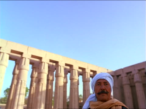 tilt down PORTRAIT Egyptian man in front of large columns / Court of Amonhotep III /Temple of Luxor / Egypt