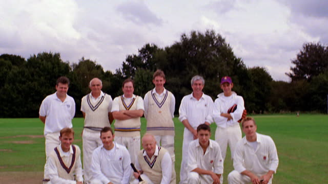 tilt down PORTRAIT from sky to cricket players posing together for camera on field / Hertfordshire, England