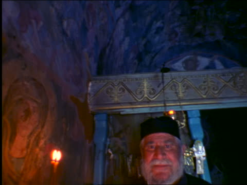 tilt down portrait greek orthodox priest with candles in byzantine church looking at camera / crete, greece - religiöse kleidung stock-videos und b-roll-filmmaterial