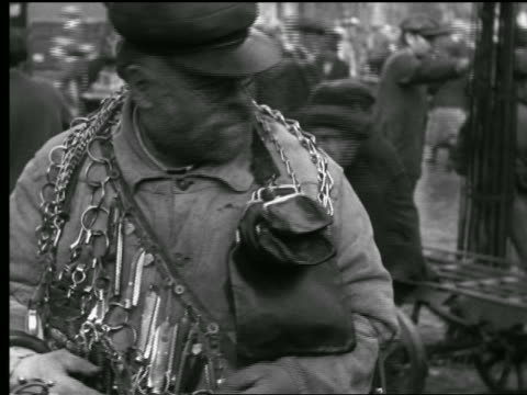 B/W 1927 tilt down PORTRAIT man wrapped in chains, razors + leather straps he is selling on street / Paris