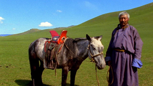 stockvideo's en b-roll-footage met tilt down portrait middle-aged asian man standing with horse nodding head on green hillside / mongolia - mongolië