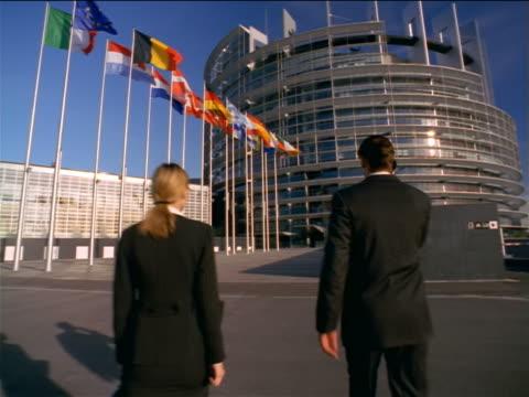 tilt down REAR VIEW businessman + woman walking towards EU Parliament building / Strasbourg, France