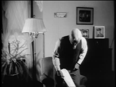 B/W 1943/44 tilt down senior man sits down in chair, turns on lamp + reads newspaper in living room