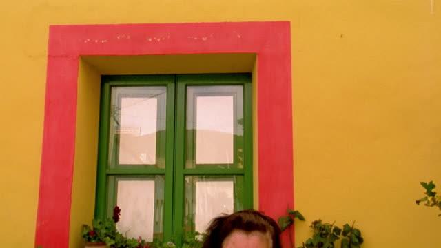 vídeos de stock e filmes b-roll de ms tilt down senior woman looking at camera with plants + flowers on windowsill behind her / linosa, sicily - peitoril de janela
