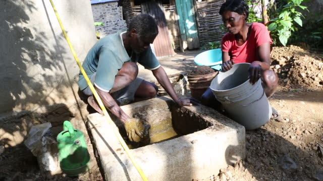 a tilt down shot of a farmer couple who are preparing dung for the production of biogas in a rural area near pilate haiti - afro caribbean ethnicity stock videos and b-roll footage