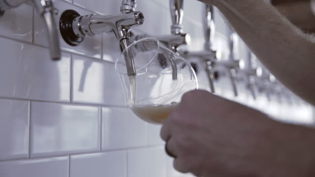 vídeos de stock e filmes b-roll de tilt down shot of brewer filling wineglass with beer tap at brewery - provar