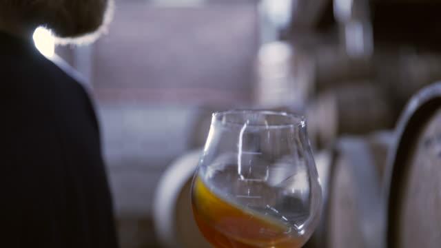 vídeos de stock, filmes e b-roll de tilt down shot of brewer tasting beer at warehouse - barril