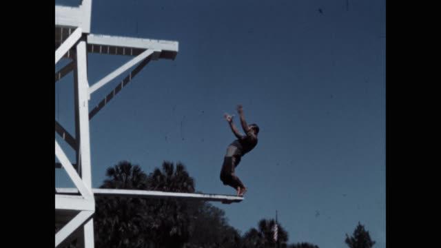 vidéos et rushes de tilt down shot of clown diver diving into lake - hobbies