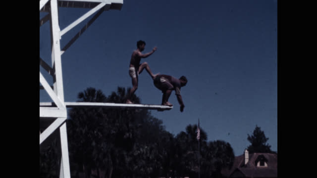tilt down shot of coach pushing clown diver into lake - shirtless stock videos & royalty-free footage