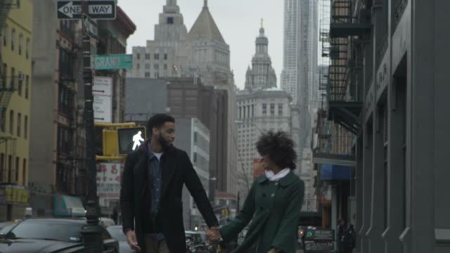 vidéos et rushes de tilt down shot of couple kissing while walking on footpath in city - embrasser sur la bouche
