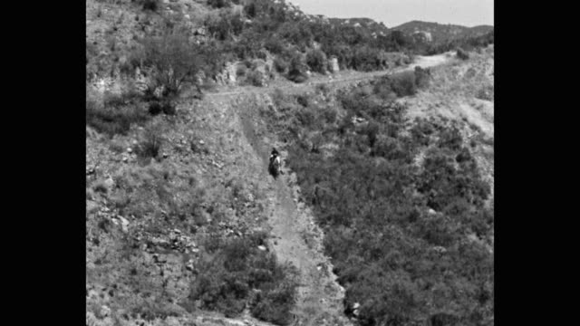 stockvideo's en b-roll-footage met tilt down shot of cowboy riding horse on hill - alleen één mid volwassen man