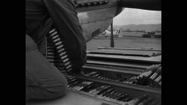 tilt down shot of crewman loading ammunition into wing of p-51 mustang on runway at taegu air base, south korea - three quarter length stock videos & royalty-free footage