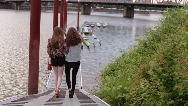vídeos de stock e filmes b-roll de tilt down shot of female friends walking on pier over river in city - rio willamete