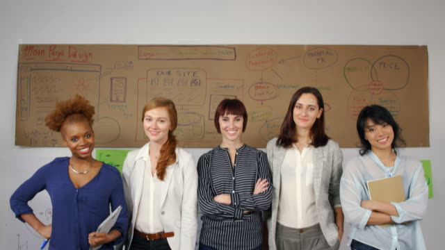 tilt down shot of happy businesswomen standing against wall in creative office - stand stock videos & royalty-free footage