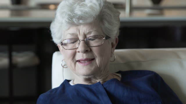 stockvideo's en b-roll-footage met tilt down shot of home caregiver consoling senior woman in living room - opluchting