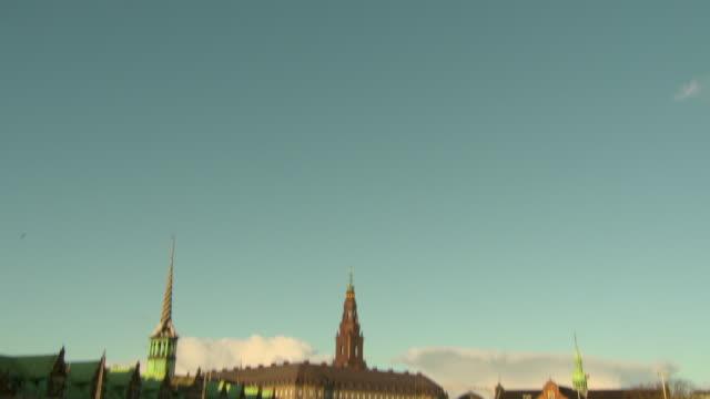 vídeos de stock e filmes b-roll de tilt down shot of landmarks and buildings by canal in city against sky - copenhagen, denmark - pináculo campanário
