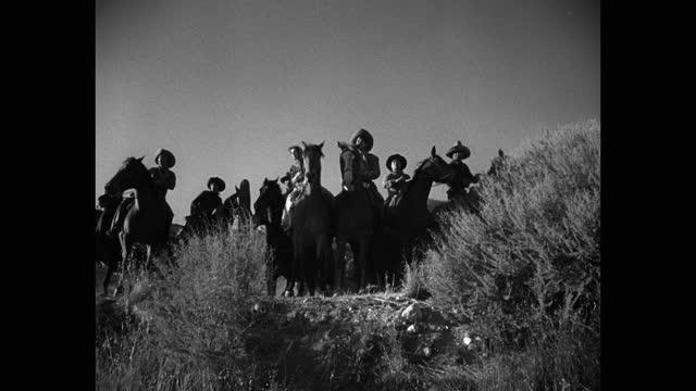 stockvideo's en b-roll-footage met tilt down shot of men riding horses in desert - western usa