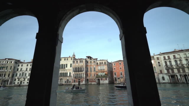tilt down shot of motorboats in canal against buildings seen through archway - fianco a fianco video stock e b–roll
