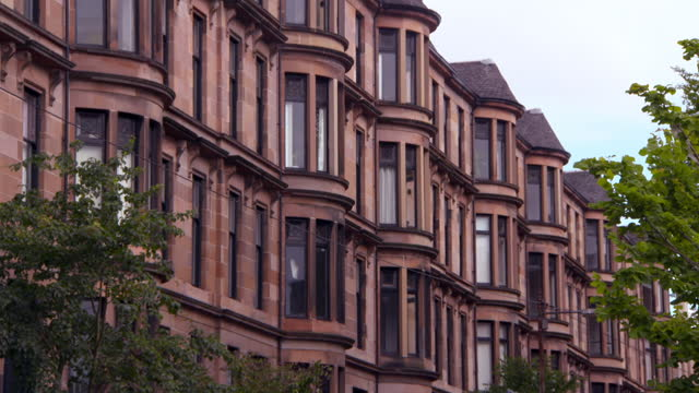 tilt down shot of residential building in city against sky - glasglow, scotland - tilt down stock videos & royalty-free footage