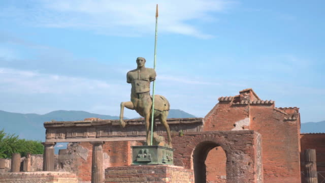 tilt down shot of statue of centaur at historic old ruin against sky, stone sculpture in city on sunny day - pompeii, italy - 遺跡点の映像素材/bロール