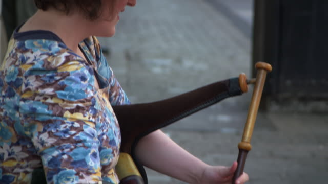 tilt down shot of street musician playing musical instrument in city - galway, ireland - focus on foreground stock videos & royalty-free footage