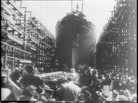 tilt down shot of uss iowa battleship in shipyard / 65000 tons surpassing next largest warship by 10000 / eleanor roosevelt walks past camera smiling... - henry j. kaiser stock videos and b-roll footage