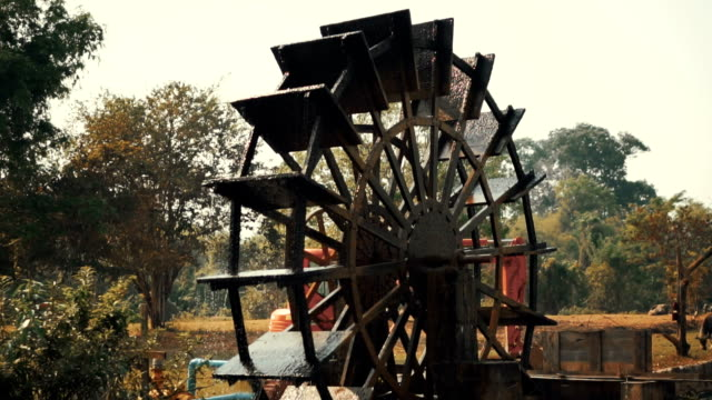 slo mo tilt down shot of water wheel turning slowly through water - water wheel stock videos and b-roll footage