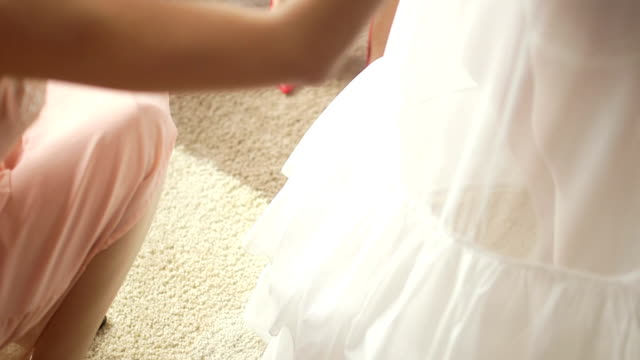 Tilt down shot of woman dressing up bride. Cropped image of female buttoning wedding dress. She is fastening pearl buttons of jacket.
