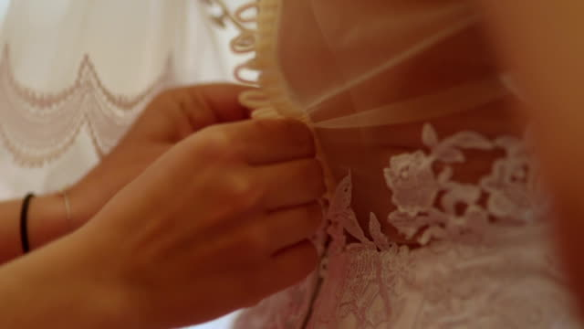 Tilt down shot of woman dressing up bride.