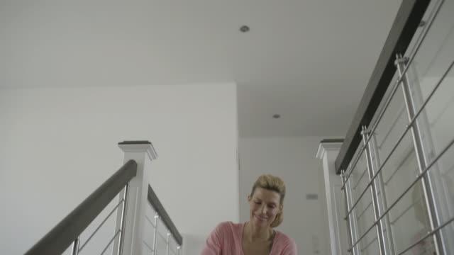 vídeos de stock, filmes e b-roll de tilt down shot of woman using smart phone while sitting on steps after workout at home - só uma mulher madura