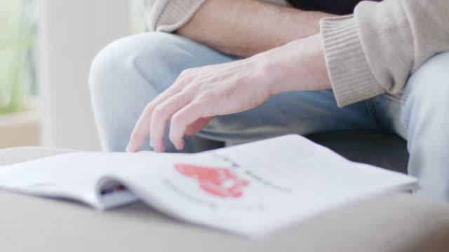 vídeos de stock e filmes b-roll de tilt down shot of young man reading book at home - revista publicação