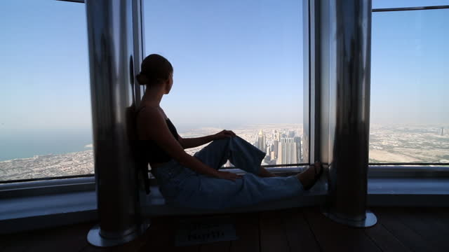 tilt down shot of young woman looking through window at dubai city on sunny day - fensterfront stock-videos und b-roll-filmmaterial