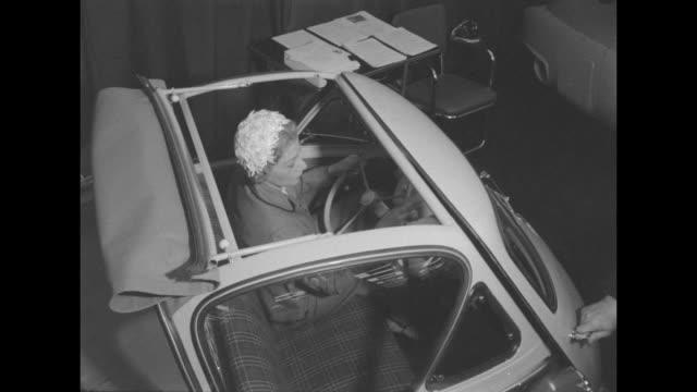 tilt down shot woman gets into Isetta Kleinwagen car via a frontopening door and shuts the door open roof flap reveals her inside the car and male...