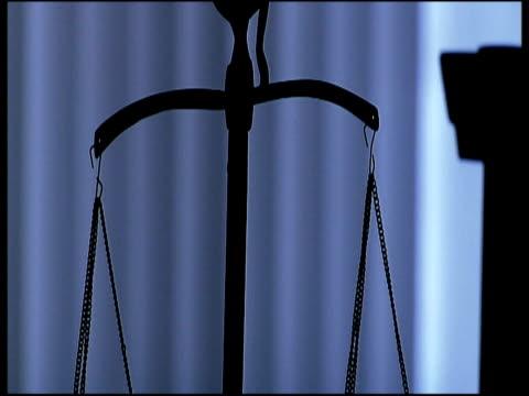 vidéos et rushes de tilt down silhouetted balance scales symbolizing justice - balance