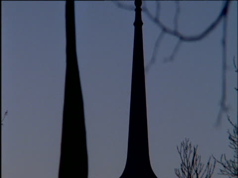 vídeos y material grabado en eventos de stock de tilt down silhouetted church spire with bare branches behind - chapitel
